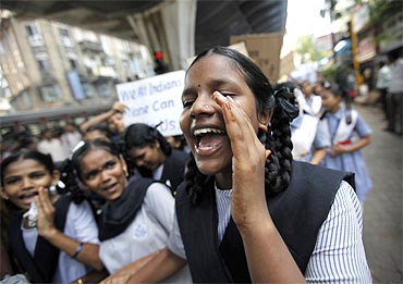 A schoolgirl shouts slogans during a rally organised by a non-governmental organisation to appeal for peace and calm in Mumbai