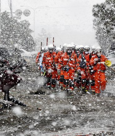 Heavy snow falls on rubble and rescue workers at a devastated factory area hit by an earthquake and tsunami in Sendai