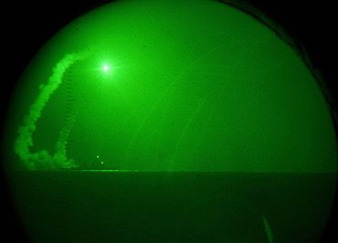 Seen through night-vision lenses aboard amphibious transport dock USS Ponce, the guided missile destroyer USS Barry fires Tomahawk cruise missiles in support of Operation Odyssey Dawn