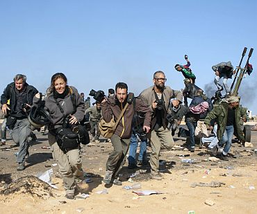 Journalists, including New York Times photographer Tyler Hicks (R- in glasses), Getty Images photographer John Moore (2nd L), freelance photographer Holly Pickett (3rdL) and freelancer Philip Poupin (4th L) run for cover during a bombing run by Libyan government planes at a checkpoint