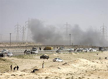 Smoke from a tank shell explosion rises over rebel vehicles just outside the northeastern Libyan town of Ajdabiyah