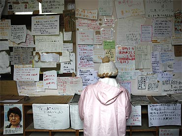 A woman looks at a list of victims and survivors at a shelter for victims in Otsuchi