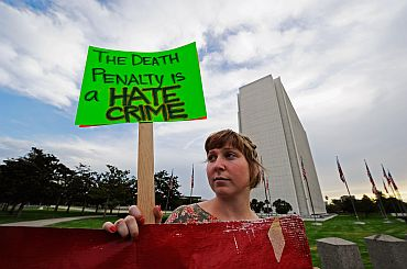 An anti-death penalty protester holds a placard during a rally and a march in front of the Federal Building in Los Angeles