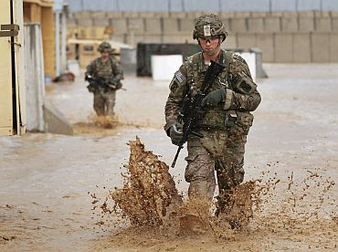 US army soldiers walk through water after a flash floods near Kandahar