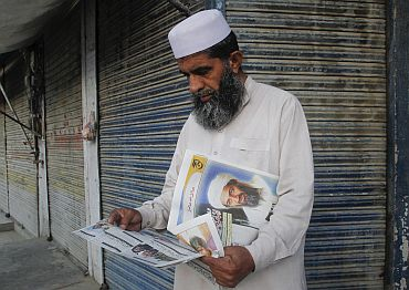 A man reads a local newspaper reporting the death of al-Qaeda leader Osama bin Laden in Abbottabad