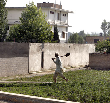 A resident farmer walks past the compound where Al Qaeda leader Osama bin Laden was killed in Abbottabad