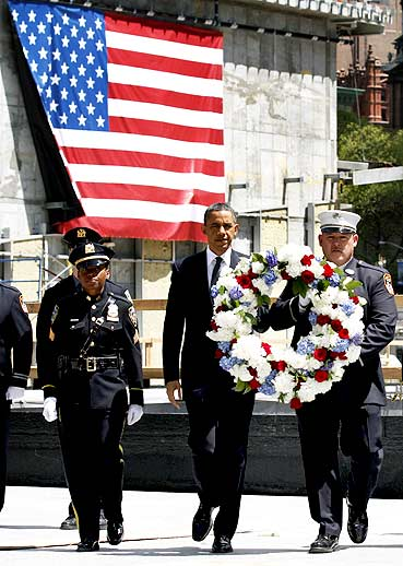 US President Barack Obama carries a wreath accompanied by New York City firefighters and police officers during a visit to the World Trade Center site