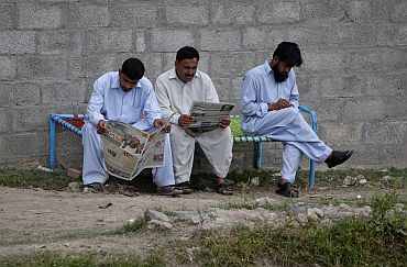 Men read newspapers while sitting near the compound where US Navy SEAL commandos reportedly killed bin Laden in Abbottabad
