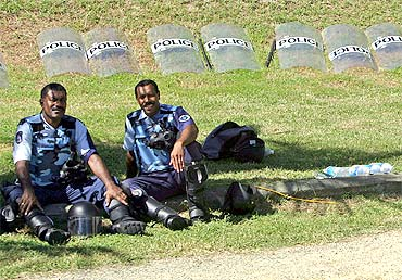 Policemen rest in front of a row of riot shields on the grounds of the country's Parliament House