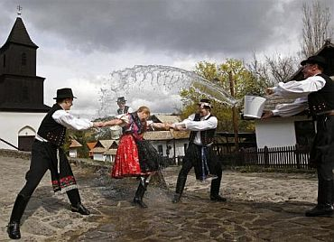 Men hold onto a woman as they throw water at her as part of traditional Easter celebrations, during a media presentation in Holloko, 100 km east of Budapest, on April 14, 2011. Locals from the World Heritage village of Holloko, celebrate Easter with the traditional 'watering of the girls', a Hungarian tribal fertility ritual rooted in the area's pre-Christian past