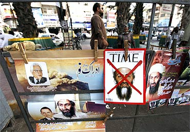A newspaper stand displays magazines and posters bearing the pictures of Osama bin Laden