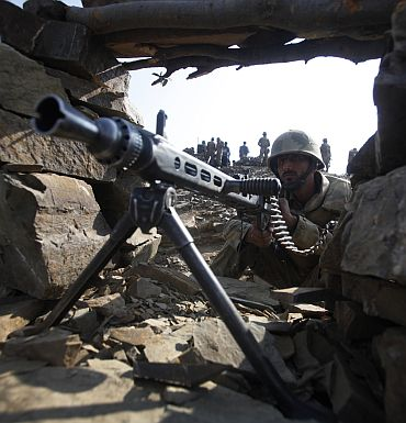 A Pakistani soldier holds a machine gun as he poses for the media during an operation organized by the army on top of a mountain near Sherwangi Tor village, located in South Waziristan