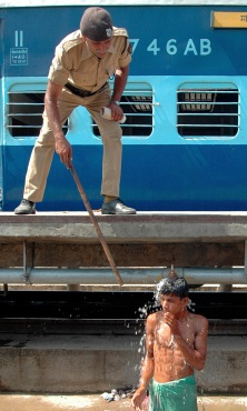 A policeman tries to stop a boy from taking bath from railway hose pipe in Patna