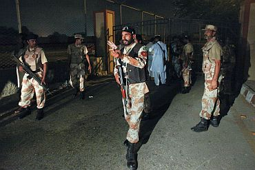 Military officials gesture to journalists to stay away at an entrance to the Mehran naval aviation base