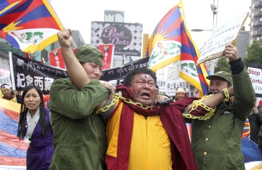 Activists dressed as Chinese soldiers and a Tibetan monk perform a street drama depicting Tibet's uprising 52 years ago against Chinese rule, in Taipei