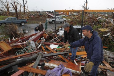 Volunteers look for survivors in the rubble of a home after a devastating tornado hit Joplin