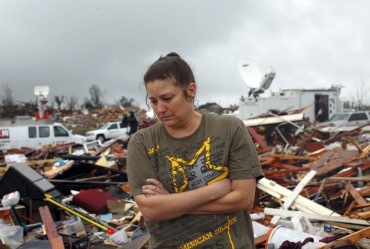 A woman looks through debris