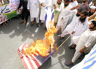 Supporters of Jamaat-ud-Dawa set fire to Israeli and US flags during a protest rally in Lahore