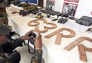 A soldier takes pictures of seized ammunition from Kashmiri militants, supplied by the LeT