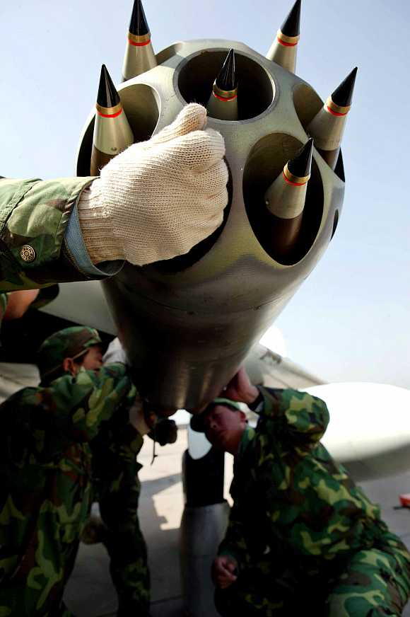 Chinese air force soldiers arm a plane during an exercise at a military base in Jinan