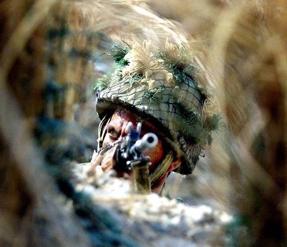 An Indian soldier keeps guard from a bunker, close to the India-Pakistan border, some 52 km from Jammu