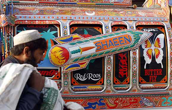 A man walks past a vehicle decorated with an image of a nuclear-capable Shaheen missile in Rawalpindi