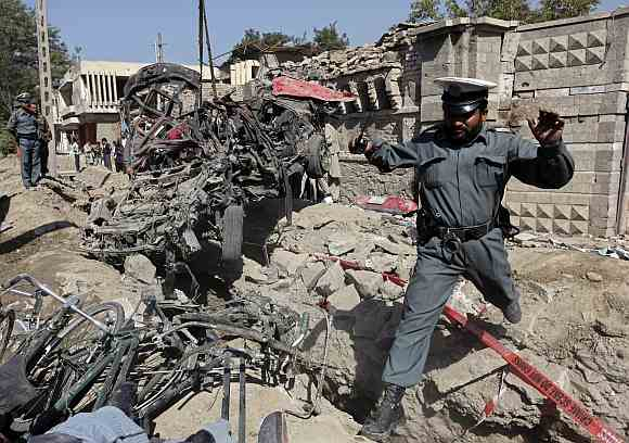 An Afghan policeman jumps over debris as he investigates at the site of a blast outside the Indian embassy in Kabul