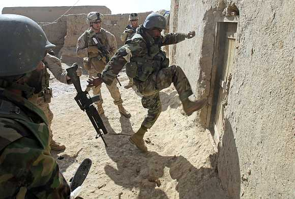 An Afghan soldier attempts to break open a door as US Marines from Bravo Company of the 1st Battalion, 6th Marines, look on during an operation to search for weapons in the town of Marjah, in Nad Ali district of Helmand province.