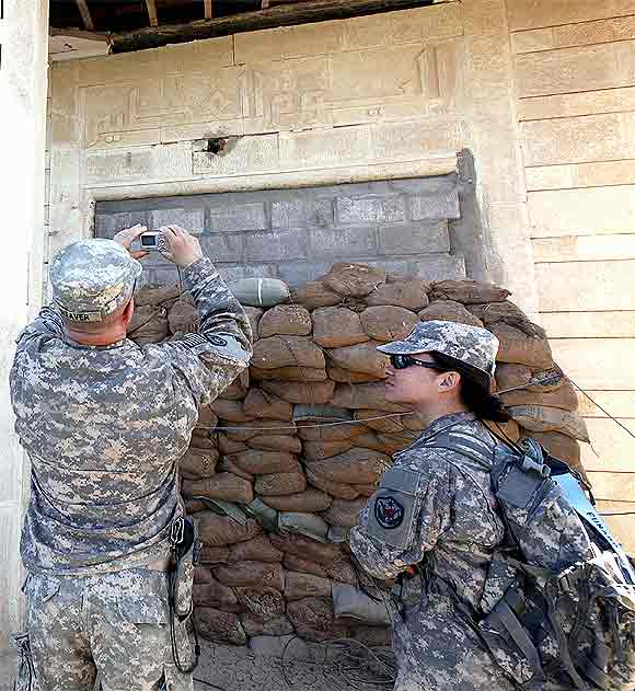 A US soldier takes a photograph of Arabic words