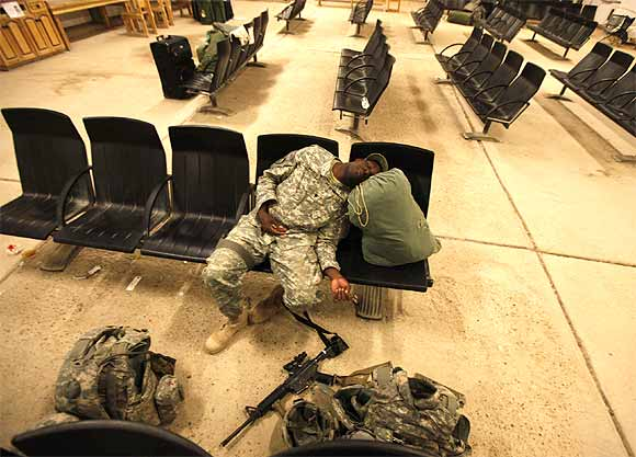 A member of the US Air Force rests in a hall, before flying to the US, at al-Asad air base in Iraq's western province of Anbar