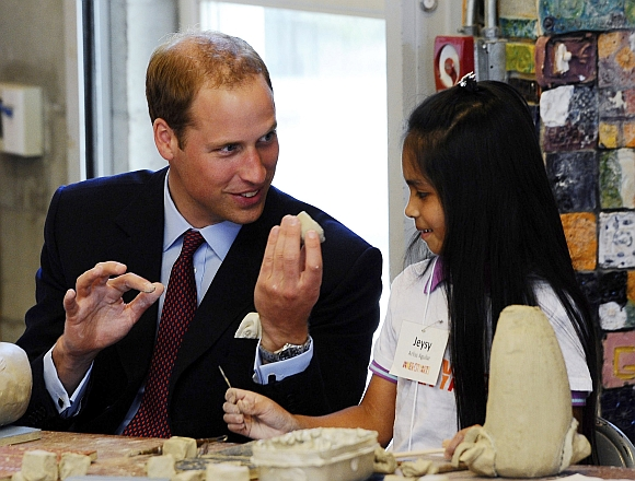 Britain's Prince William shows a piece of clay to Jeysy Aguilar during a ceramics class at the Inner-City Arts campus in Los Angeles California