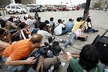 Photographers and members of the media cover a gunfire at the Taj Hotel in Mumbai during the 26/11 attacks