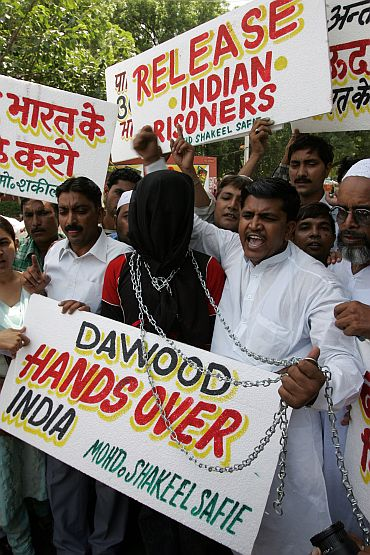 Muslims hold placards and shout slogans during a protest in New Delhi demanding that Pakistan must handover Dawood Ibrahim
