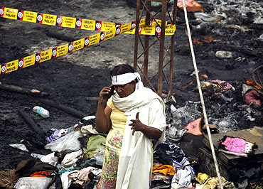 A eunuch speaks on a mobile phone at the site of Sunday's fire