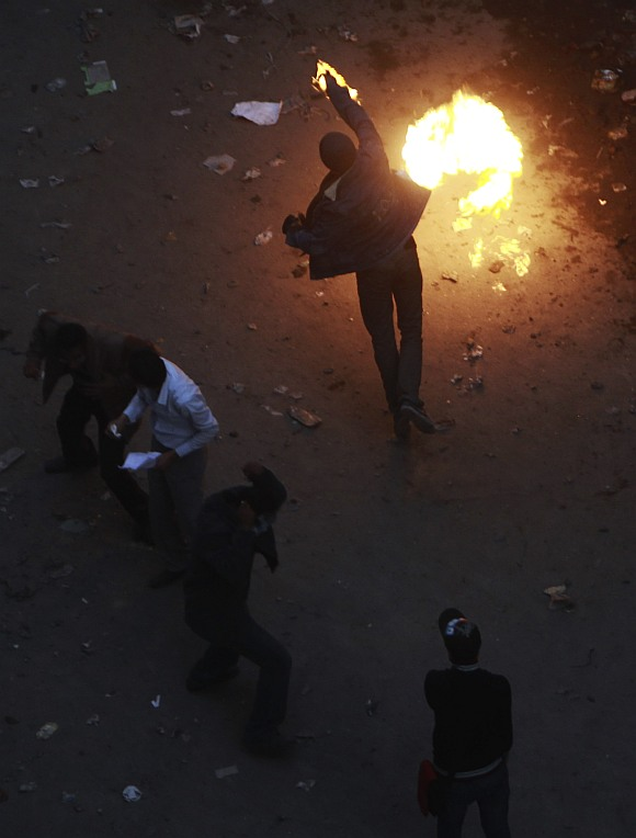 A protester throws a Molotov cocktail (petrol bomb) at riot police during clashes along a road which leads to the Interior Ministry, near Tahrir Square in Cairo