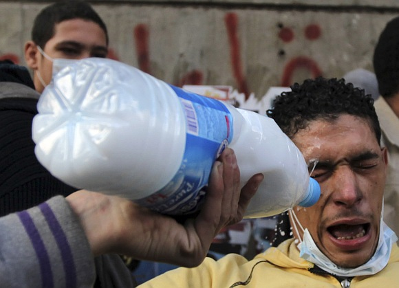 A protester has his eyes washed with milk to protect against tear gas during clashes with riot police along a road which leads to the Interior Ministry, near Tahrir Square in Cairo