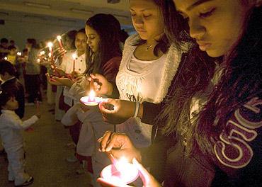 People light candles during a candlelight vigil after 26/11