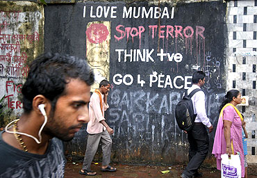 Pedestrians walk past graffiti that was painted after the 26/11 attacks outside a crematorium in Mumbai