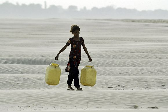 A village girl carries empty containers to collect drinking water near Chilla village in the Bundelkhand region, which may form a separate state carved out of UP