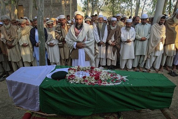 Relatives and residents pray near the flag-draped coffin of solider Najeebullah, who was killed in a Nato cross-border attack