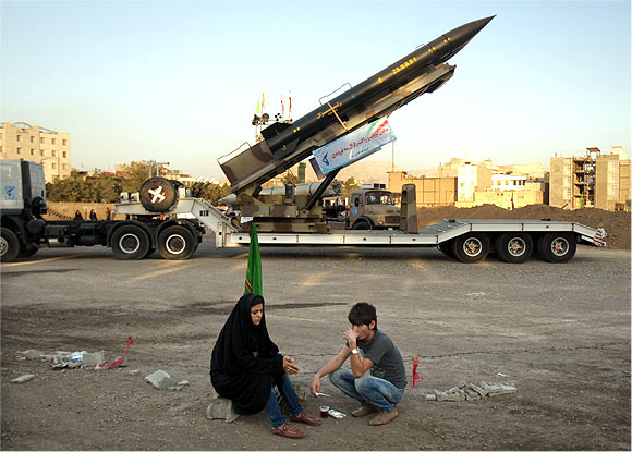 A couple rests as they sit in front of an Iranian-made Zelzal missile at a war exhibition