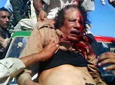 A fighter pulls Libya's former leader Muammar Gaddafi onto a miltary vehicle in Sirte in this still image taken from a video