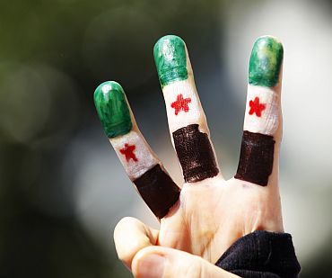 A Syrian opposition demonstrator, her fingers painted with the colours of Syrian flag
