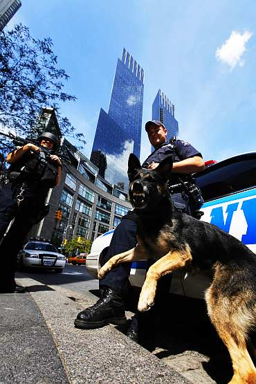 A New York Police Department Hercules team member holds his dog as he patrols near Columbus Circle in New York
