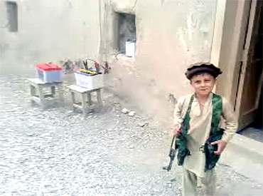A child smiles while carrying a weapon in an undisclosed location in Pakistan's northwest region