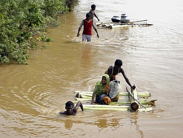 Flood-affected villagers make their way to safer place in Dihasai Biri village