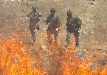 Afghan policemen are seen behind a pile of burning narcotics in Kabul