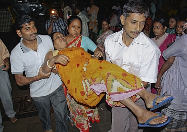 A woman, who was injured by a stampede after an earthquake, is carried to a hospital in  Siliguri