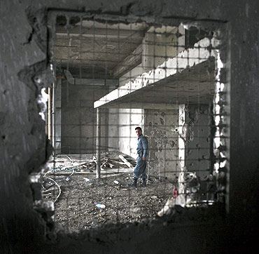 An Afghan policeman inspects a building after a battle with Taliban insurgents near the US embassy