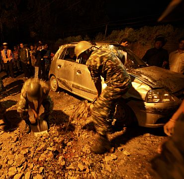 Members of the Nepalese army clear stones around a damaged car after the wall surrounding the British embassy collapsed during the 6.8 magnitude earthquake